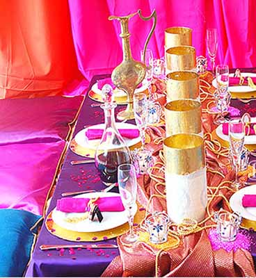 blue pink and purple decorative fabrics with golden candles and pink napkins for arabian nights theme party table decoration