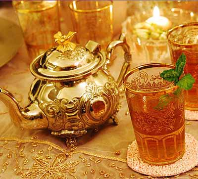 glass with mint tea and golden tea pot for arabian nights theme party table decoration