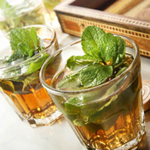 a glass with mint tea and green leaves moroccan style drink