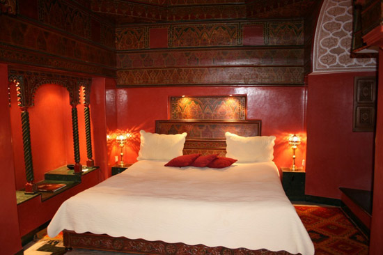 moroccan bedroom decorating ideas include red wall paint and wooden decorations