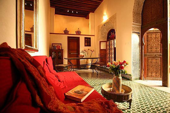 red decorating fabrics and dark wooden door for moroccan decorating style