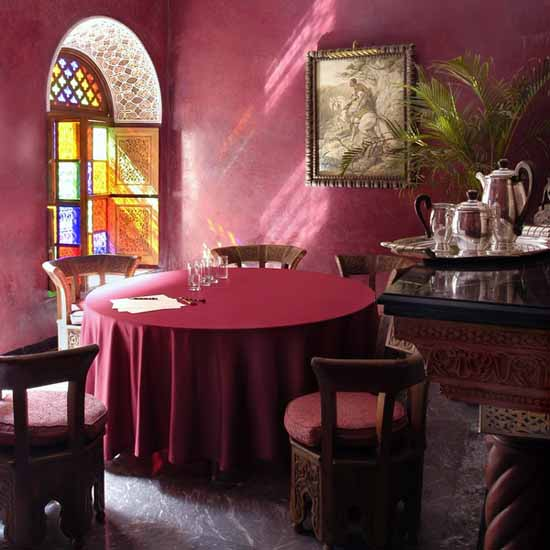 moroccan style dining room ideas with round table and pink wall paint and tablecloth