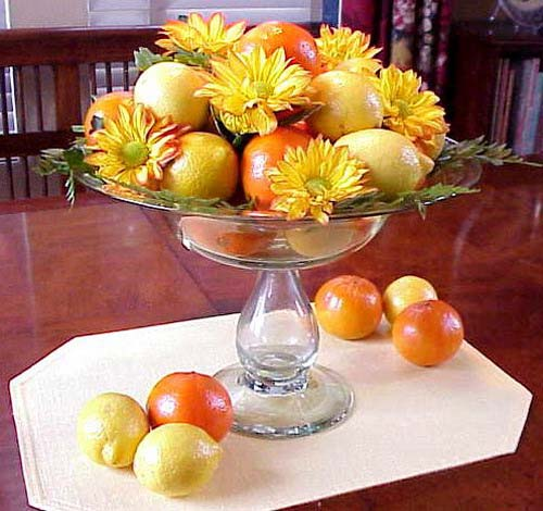 orange and yellow flowers and citrus fruits create festive table flower arrangements