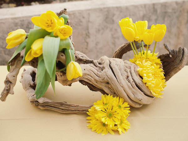 yellow tulips and carnations with drift wood make a beautiful table centerpiece