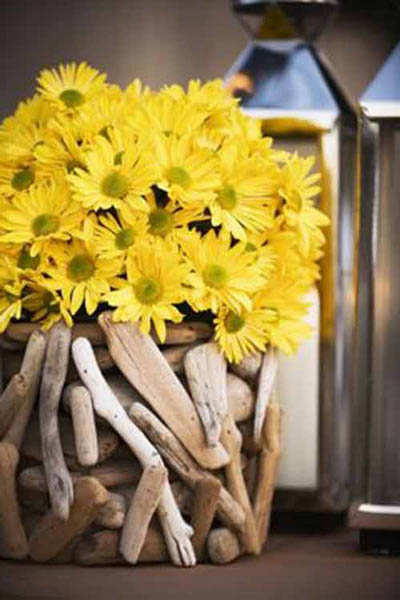 yellow daisies and drift wood collected in a glass vase make unique table centerpiece