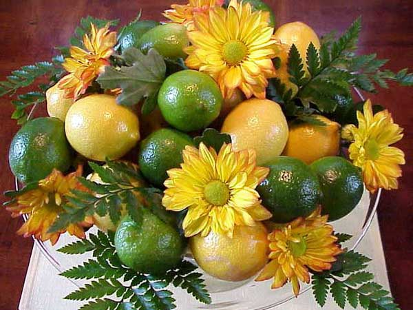 yellow mums and daisies with green leaves and citrus fruits are great centerpiece ideas