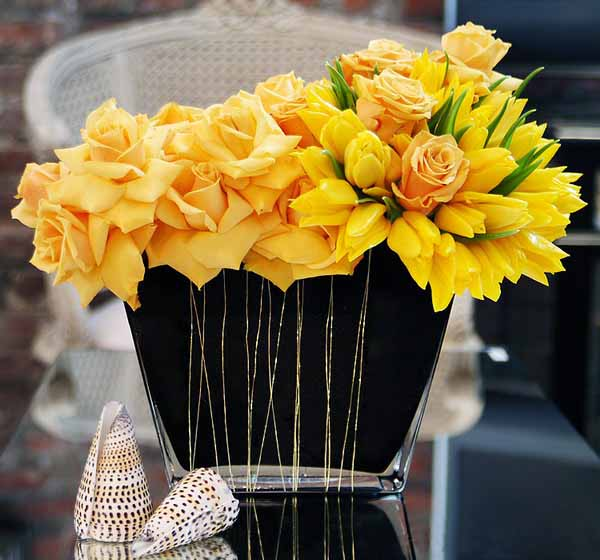 yellow roses and sea shells create unique table centerpiece