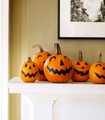 fireplace decorating with smiling pumpkins ad black and orange color combination