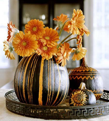 orange mums in gourd vase with carved orange stripes