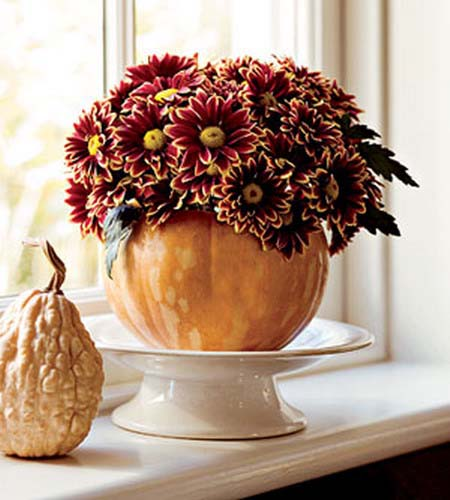 purple mums in large pumpkin vase