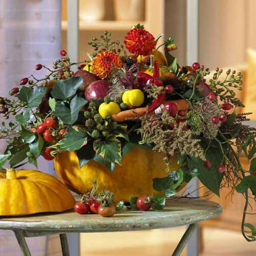 fall flowers and green leaves in pumpkin vase