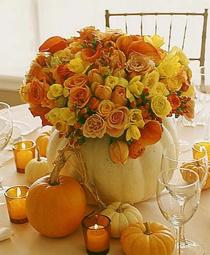 yellow and orange roses in white pumpkin vase with orange candles and mini pumpkins