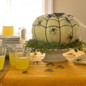 green pumpkin table centerpiece with black spiders for halloween party table decoration
