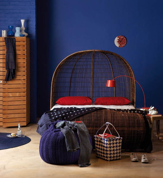 blue wall paint with african bed and red cushions