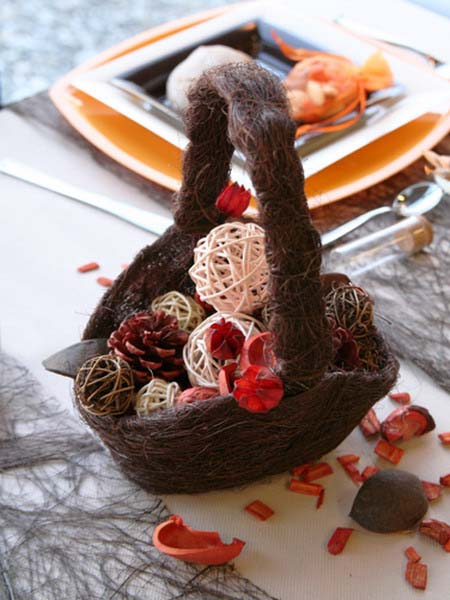 plates in orage colors and a basket with decorative balls are fall inspired centerpiece idea