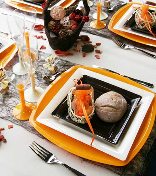 orange plates and whicker decorative balls in a basket is fall centerpiece idea