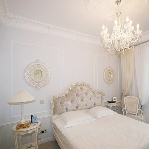 white bedroom furniture and large crystal chandelier