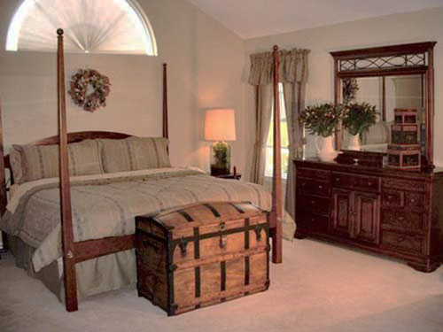 wooden chest and bed with posts in colonial style