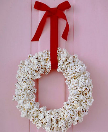 making christmas wreath of pop corn and red ribbon