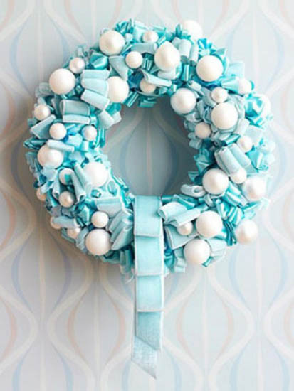 making christmas wreath of white and blue balls and ribbons