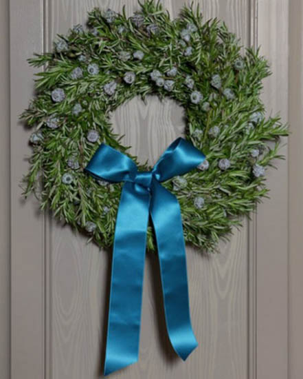 green christmas wreath with blue ribbon for wall decoration