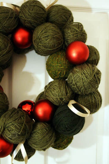 making christmas wreath of green yarn balls and red christmas balls