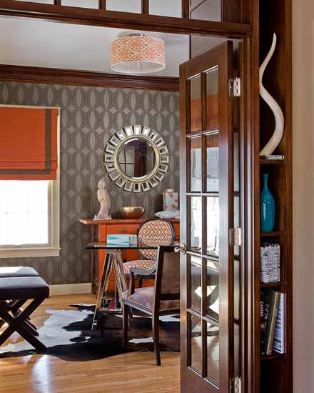 black and white wallpaper with orange furniture and curtain