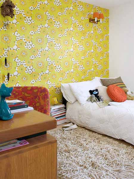 orange cushion and light green wallpaper in bedroom