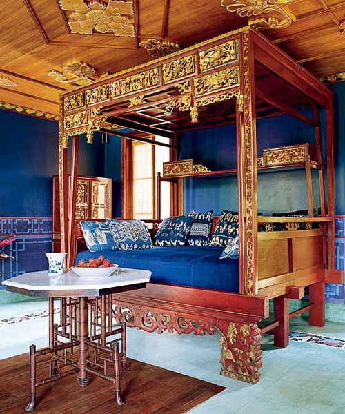 blue bedroom with carved wood bed