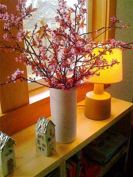 spring branches with pink flowers in ceramic vase