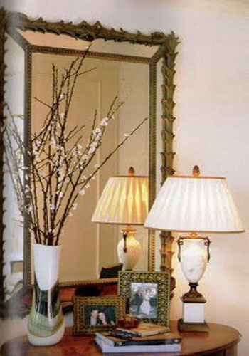 flowering branches in white vase and table lamp