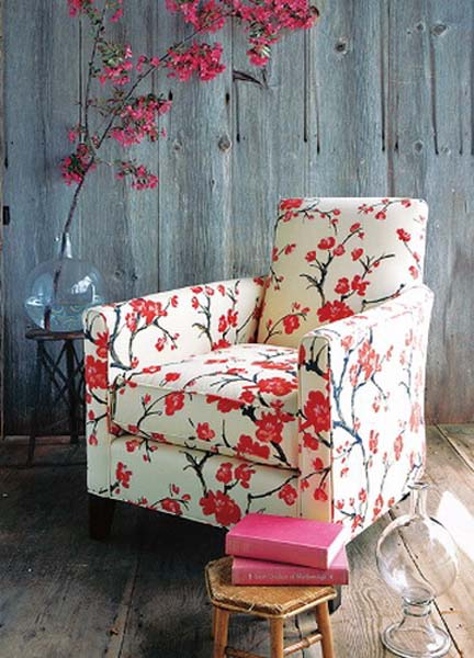 flowering branches with pink flowers and chair with floral upholstery fabric in white and pink colors