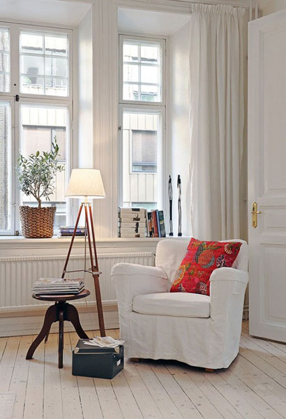white chair with red pillow and floor lamp
