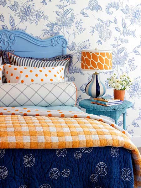 blue wallpaper pattern, blue bed headboard and night table with orange table lamp and comforter
