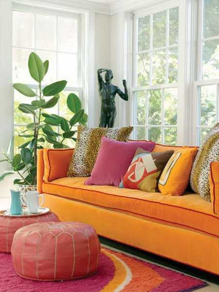 orange living room sofa with purple ottoman and pillow
