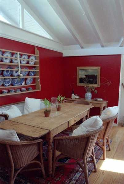 dining room with red wall and solid wood table