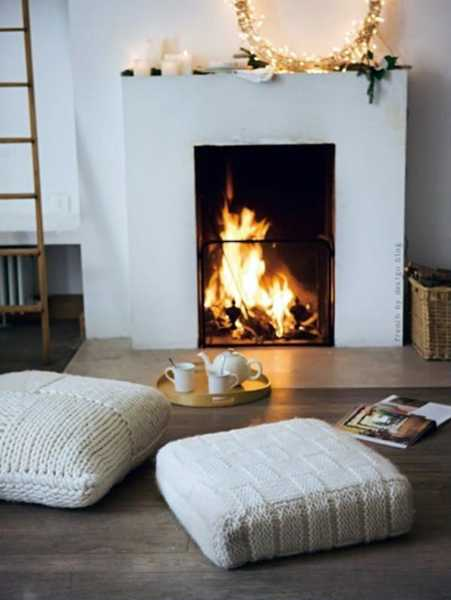 fireplace with knitted floor pillows