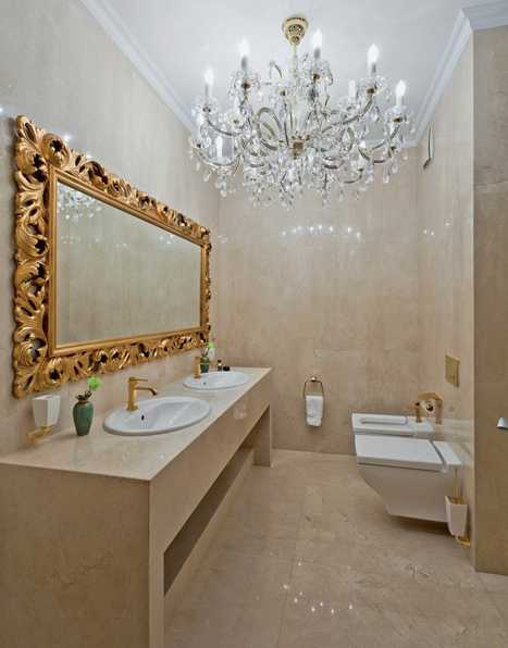 modern bathroom design with golden mirror frame and crystal chandelier
