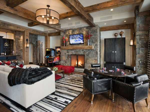 country home living room with ceiling beams and stone fireplace