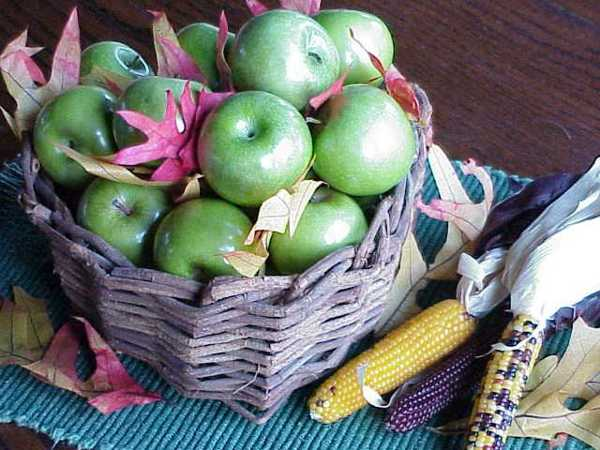 basket with green apples and fall leaves for simple thanksgiving decorating