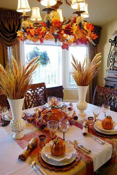 wheat heads in white vases and chandelier decorated with fall leaves
