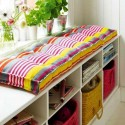 white bench with storage and colorful cushion