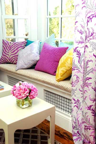 white bench with cushions and window curtains in yellow and pink colors