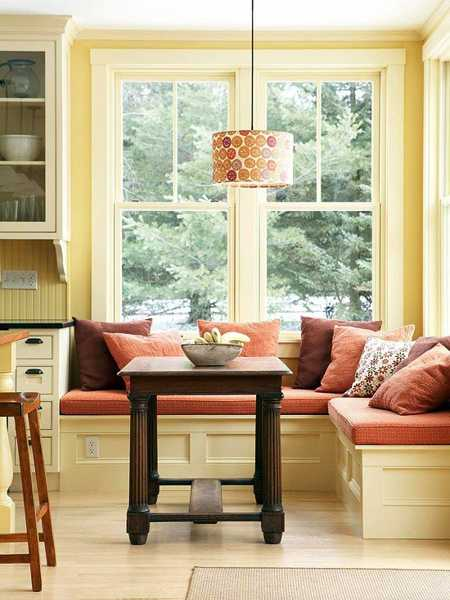 white bench with cushions in broqn and orange colors