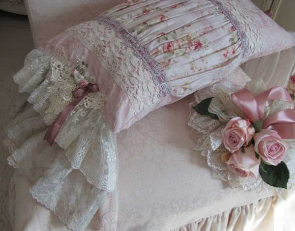 handmade pillow with roses made of lace fabric and ribbons in white and pink colors
