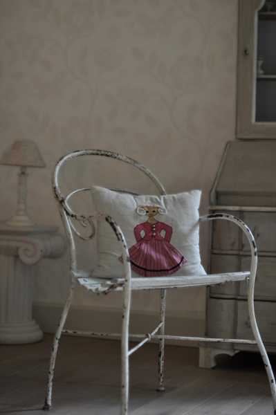 metal chair with embroidered decorative pillows