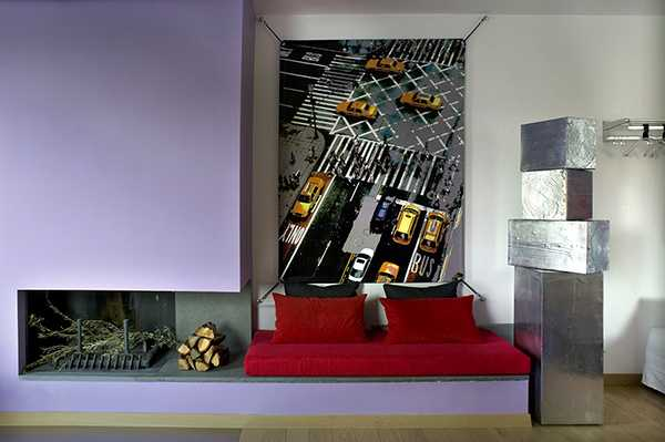 living room design with corner fireplace, steel sculpture, red sofa and large artwork