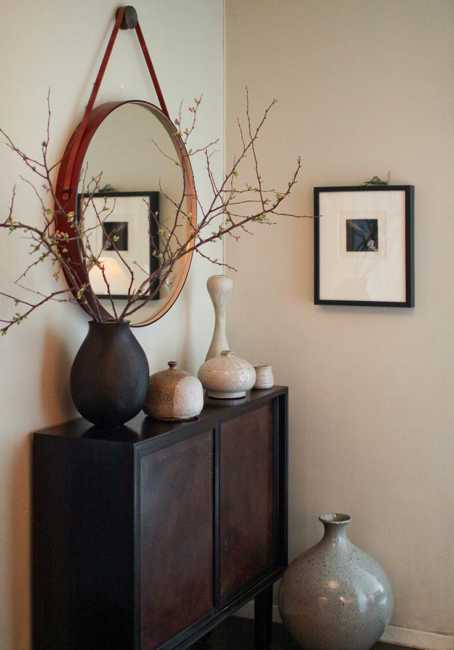 round wall mirror and decorative vases