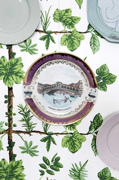 decorative plates on wall with green wallpaper