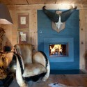 blue fireplace and unique lamp and a chair decorated with fur